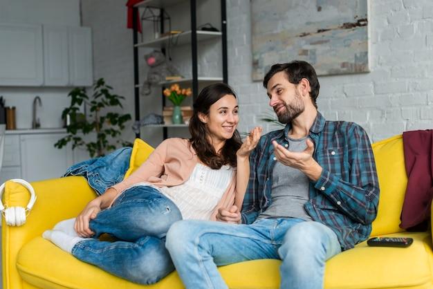 Feliz pareja hablando en el sofá Foto gratis