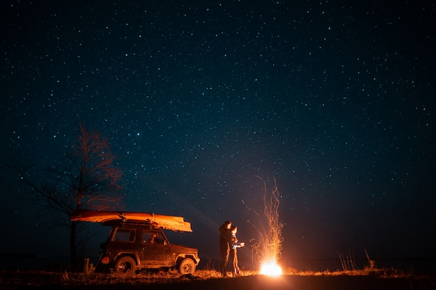 Feliz pareja hombre y mujer de pie delante de la hoguera ardiente Foto gratis