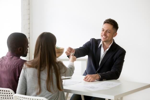 Feliz pareja interracial recibiendo las llaves de la nueva casa de la inmobiliaria Foto gratis