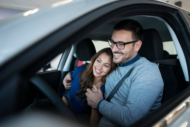 Feliz pareja joven disfrutando de su coche nuevo Foto gratis