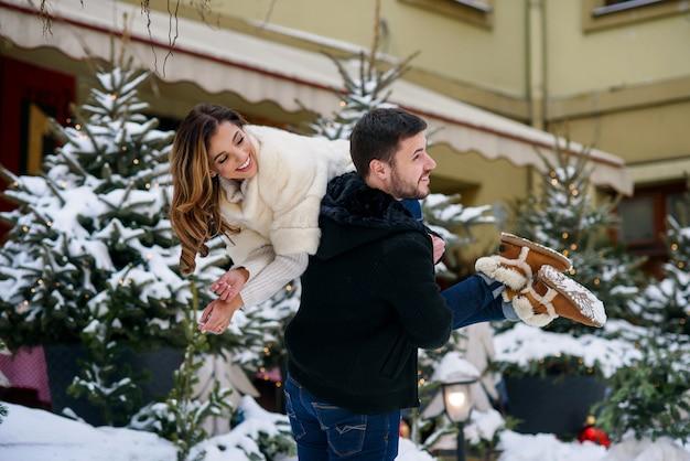 Feliz pareja joven divirtiéndose en el paisaje urbano de invierno del árbol de navidad con luces. vacaciones de invierno, navidad y año nuevo. Foto Premium