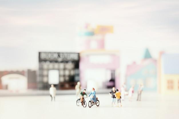 Feliz pareja joven en miniatura en bicicleta (miniatura) en bicicleta en la ciudad. día de san valentín con enfoque selectivo y tonos pastel suaves en tonos. Foto Premium