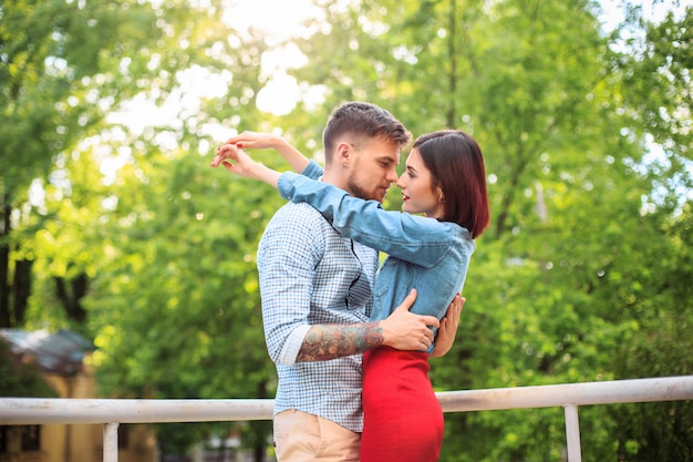 Feliz pareja joven en el parque de pie y riendo en el brillante día soleado Foto gratis