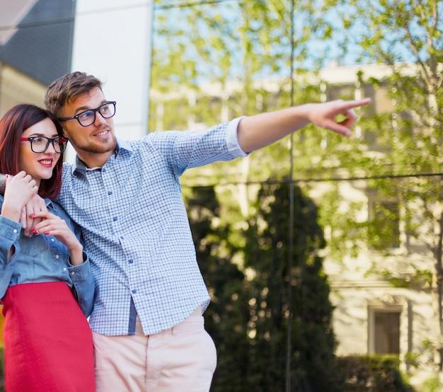 Feliz pareja joven de pie en la calle de la ciudad y riendo en el brillante día soleado Foto gratis