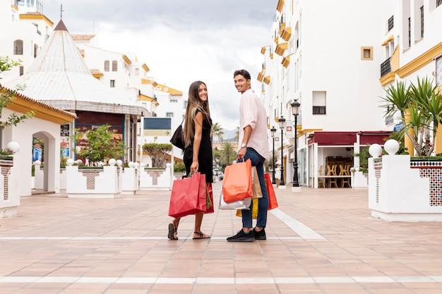 Feliz pareja mirando hacia atrás con bolsas Foto gratis