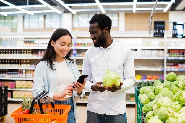 Feliz pareja multiétnica elegir productos en supermercado Foto gratis