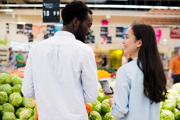 Feliz pareja multirracial elegir productos en supermercado Foto gratis