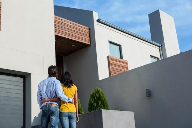 Feliz pareja de pie y mirando la nueva casa Foto Premium