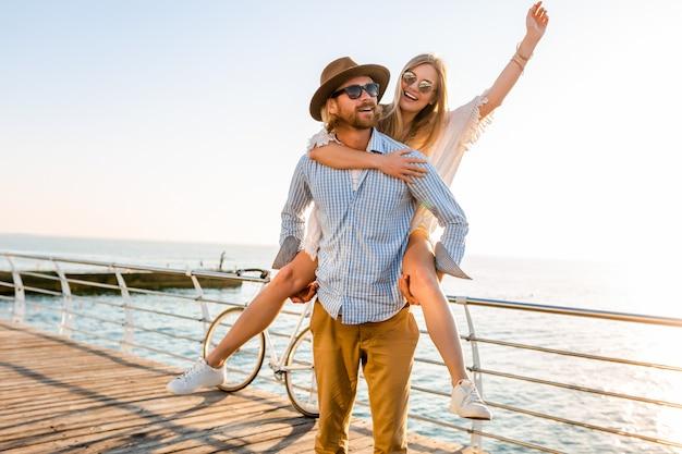 Feliz pareja riendo viajando en verano por mar, hombre y mujer con gafas de sol Foto gratis