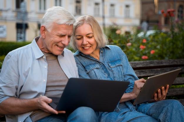 Feliz pareja senior al aire libre en un banco con ordenador portátil y tableta Foto gratis