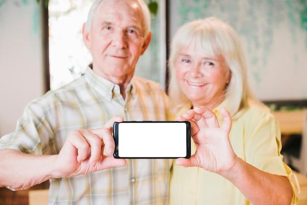 Feliz pareja senior demostrando móvil Foto gratis