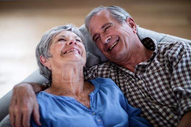 Feliz pareja senior descansando en el sofá y sonriendo Foto Premium