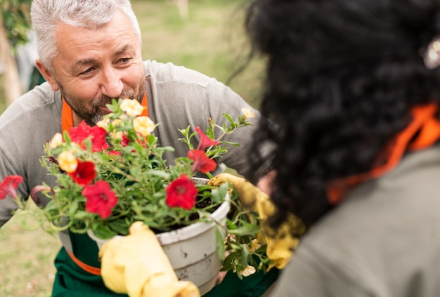 Feliz pareja senior con flores Foto gratis