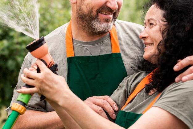 Feliz pareja senior con manguera de agua Foto gratis