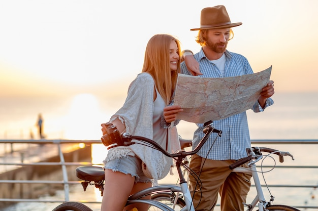 Feliz pareja viajando en verano en bicicleta, mirando en el mapa de turismo Foto gratis