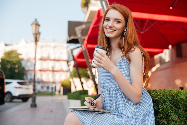 Feliz pelirroja alegre en auriculares Foto gratis