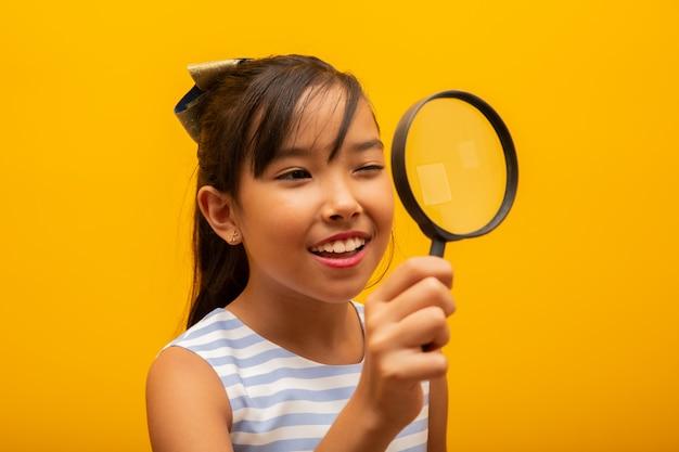 Feliz pequeño niño asiático con lupa Foto Premium