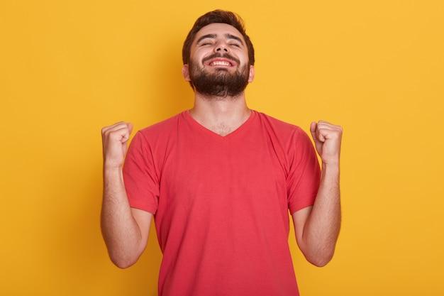 Feliz positivo emocionado joven apretando los puños y gritando, vistiendo una camiseta roja casual, teniendo buenas noticias, celebrando su victoria o éxito, gana la lotería. concepto de emociones de las personas. Foto gratis