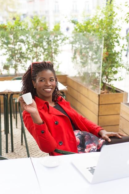 Feliz profesional independiente tomando café en la cafetería Foto gratis