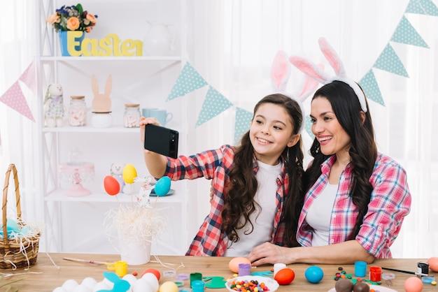 Feliz retrato de madre e hija tomando autorretrato en celular en el día de pascua Foto gratis