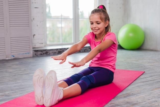 Feliz retrato de una niña sentada en una estera de ejercicios estirando sus manos Foto gratis