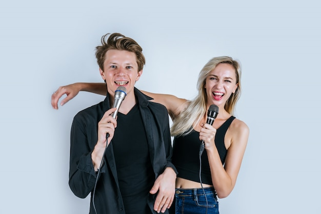 Feliz retrato de pareja con micrófono y canta una canción Foto gratis