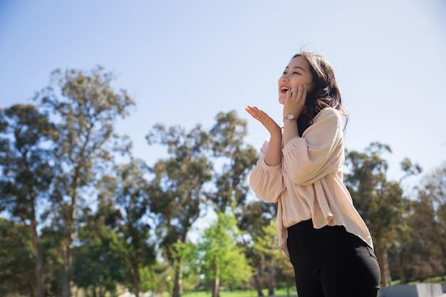 Feliz risa chica asiática totalmente emocionada con charla telefónica Foto gratis