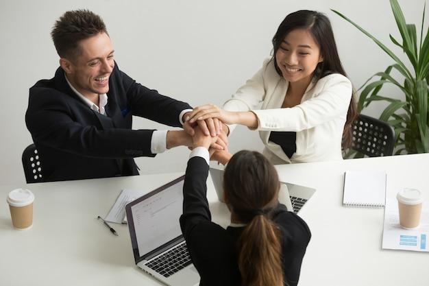 Feliz sonriente equipo diverso unir las manos en la reunión del grupo Foto gratis