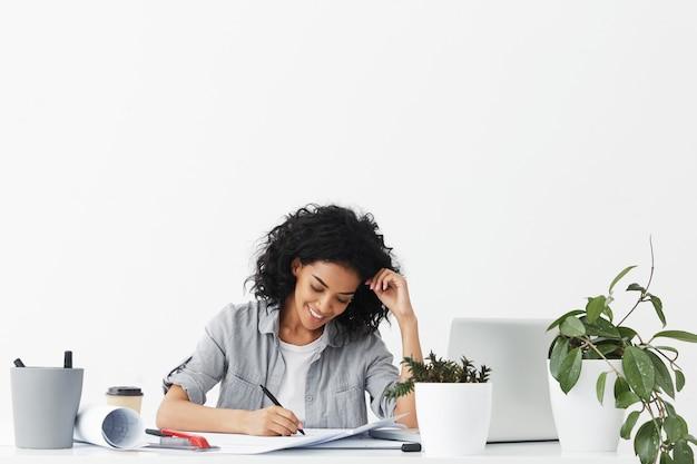 Feliz sonriente joven arquitecto afroamericano vistiendo camisa gris sobre blanco superior haciendo dibujos Foto gratis