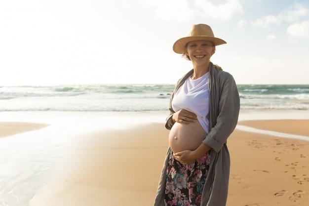 Feliz sonriente mujer embarazada cogidos de la mano en el vientre Foto gratis
