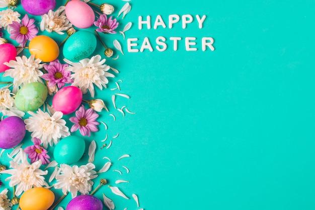 Feliz título de pascua cerca de huevos brillantes y capullos de flores Foto gratis