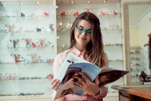 Feliz de ver las palabras claramente sin desenfoque. retrato interior de mujer europea atractiva satisfecha sentada en la tienda de óptica mientras lee la revista con gafas, esperando a que gire para comprobar la vista Foto gratis