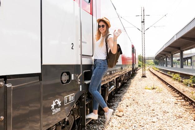 Feliz viajero sonriendo en la estación de tren Foto gratis