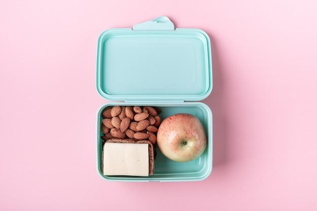 Fiambrera con manzana, sandwich y almendra en rosa. Foto Premium
