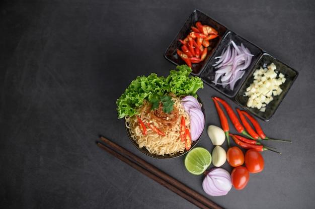 Fideos picantes en el tazón con ingredientes y palillos sobre superficie de cemento negro, vista superior Foto gratis