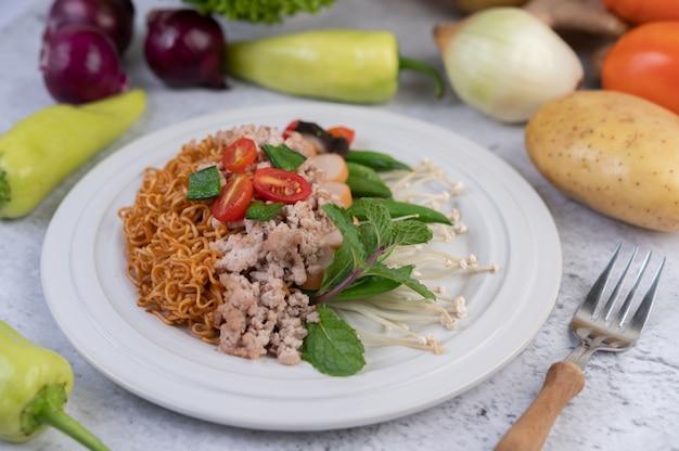 Fideos salteados con carne picada de cerdo, edamame, tomates y champiñones en un plato blanco. Foto gratis