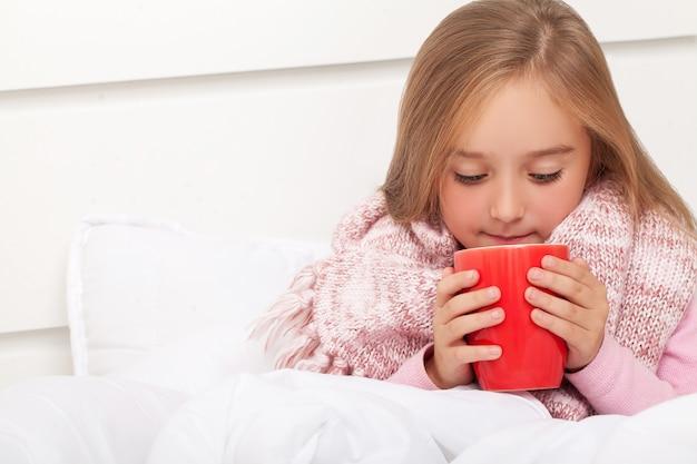 Fiebre, resfriado y gripe medicamentos y té caliente cerca, niña enferma en la cama Foto Premium