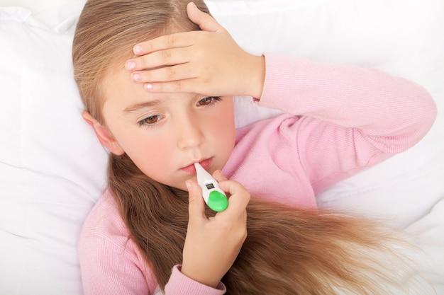 Fiebre, resfriado y gripe: medicamentos y té caliente en una niña enferma en la cama Foto Premium