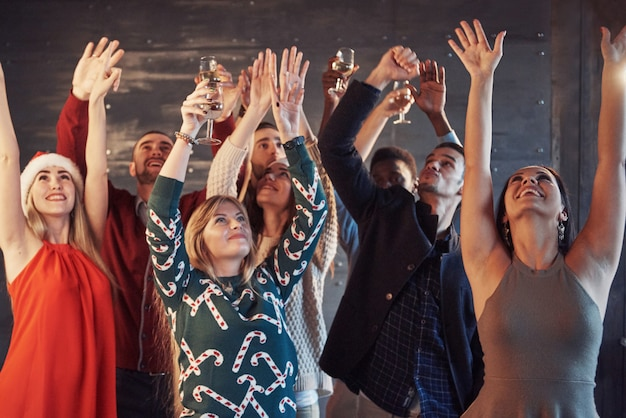 Fiesta con amigos. aman la navidad. grupo de jóvenes alegres llevando bengalas y flautas de champán bailando en fiesta de año nuevo y mirando feliz. conceptos sobre el estilo de vida de convivencia Foto Premium