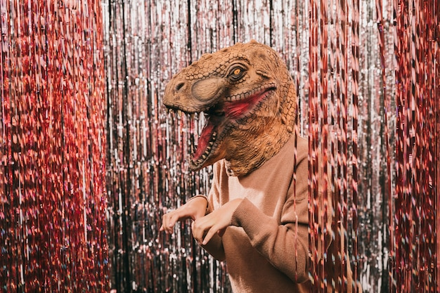 Fiesta de carnaval de alto ángulo con disfraz de dinosaurio Foto gratis