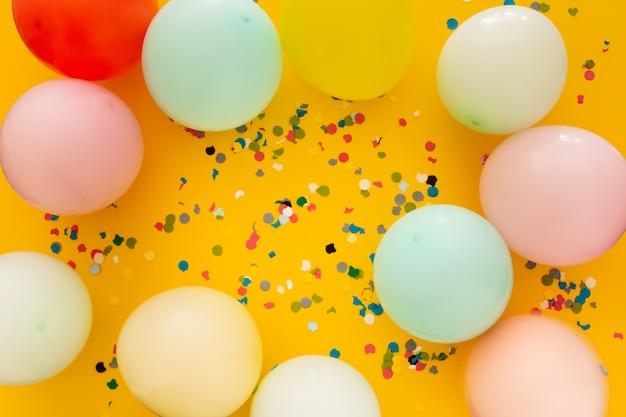 Fiesta con confeti y globos en amarillo Foto gratis