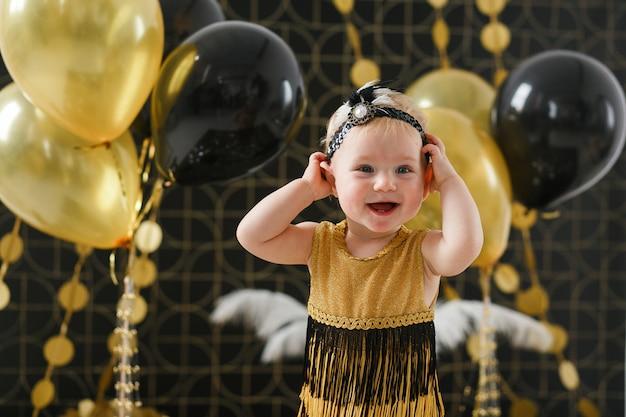 Fiesta de cumpleaños de niña bebé decorada con globo negro y dorado. Foto gratis