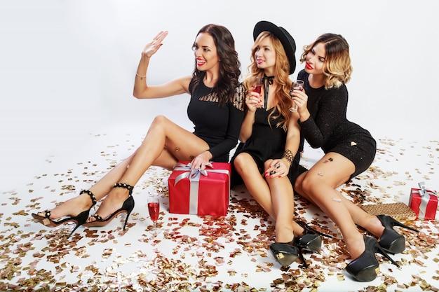 Fiesta de navidad o cumpleaños. tres hermosas mujeres sentadas en el suelo y bebiendo cócteles. los mejores amigos desempacan regalos. confeti dorado brillante. fondo blanco. peinado ondulado. Foto gratis