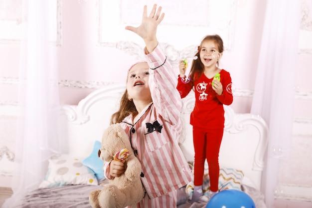 Fiesta de pijamas para niños, divertidas hermanas felices vestidas con pijamas brillantes, juego de burbujas Foto gratis