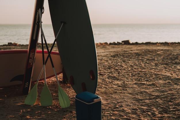 Fiesta en la playa. surfs y paletas sobre la arena. Foto Premium