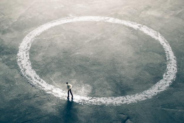 Figura en miniatura, hombres de negocios caminando por el exterior del círculo de tiza. encontrar un concepto de solución eficaz. Foto Premium