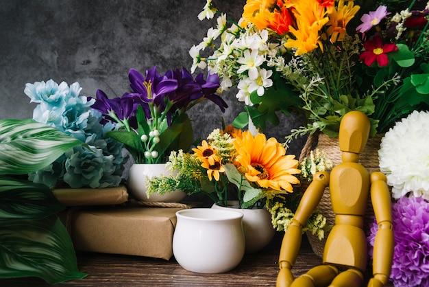 Figura simulada de madera que se sienta delante de las flores coloridas en la tabla Foto gratis