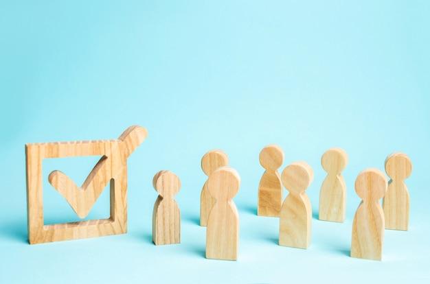Figuras humanas están juntas al lado de una marca en la casilla. el concepto de elecciones. Foto Premium