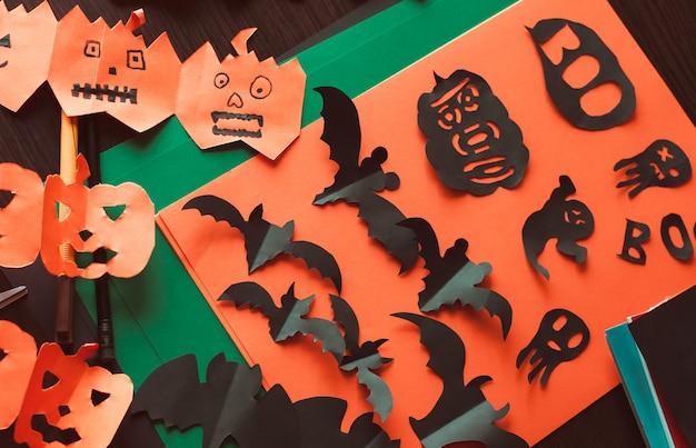 Figuras de un murciélago negro y fantasmas, una guirnalda de calabazas con caras Foto Premium