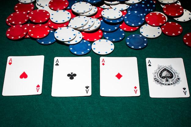 Fila de ases y fichas de casino en la mesa de póquer verde Foto Premium